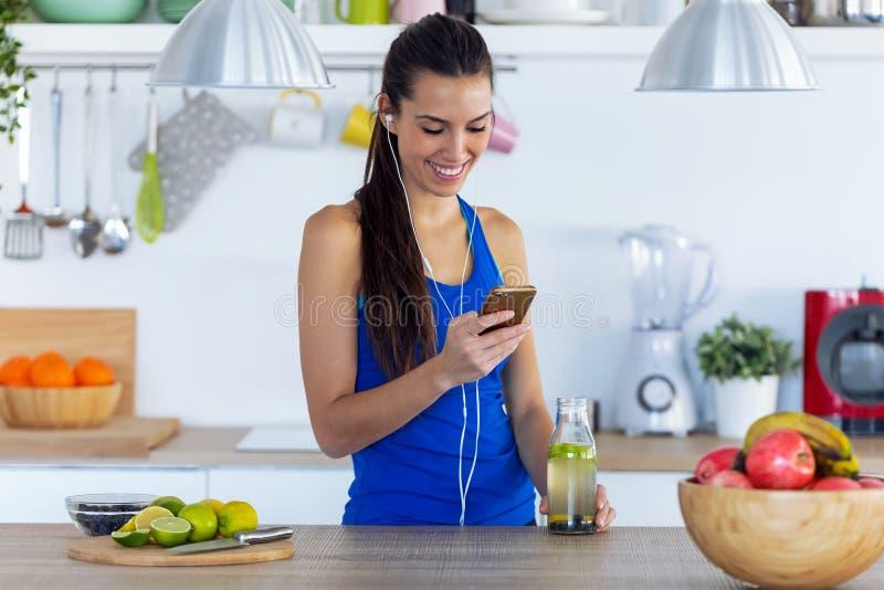 Sportig ung kvinna som lyssnar på musik med mobiltelefon efter träning i köket hemma royaltyfria bilder