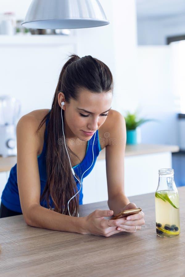 Sportig ung kvinna som lyssnar på musik med mobiltelefon efter träning i köket hemma arkivfoto