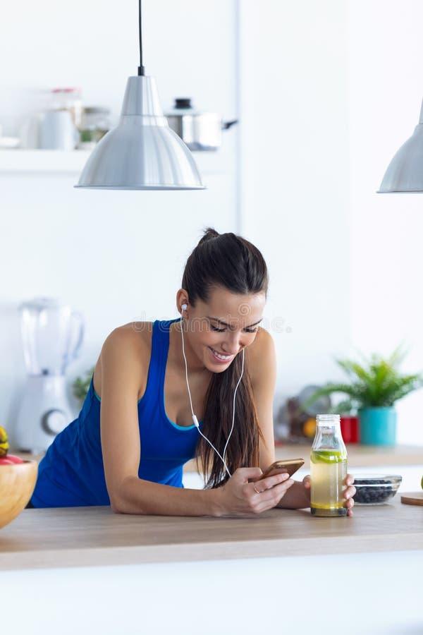 Sportig ung kvinna som lyssnar på musik med mobiltelefon efter träning i köket hemma royaltyfria foton