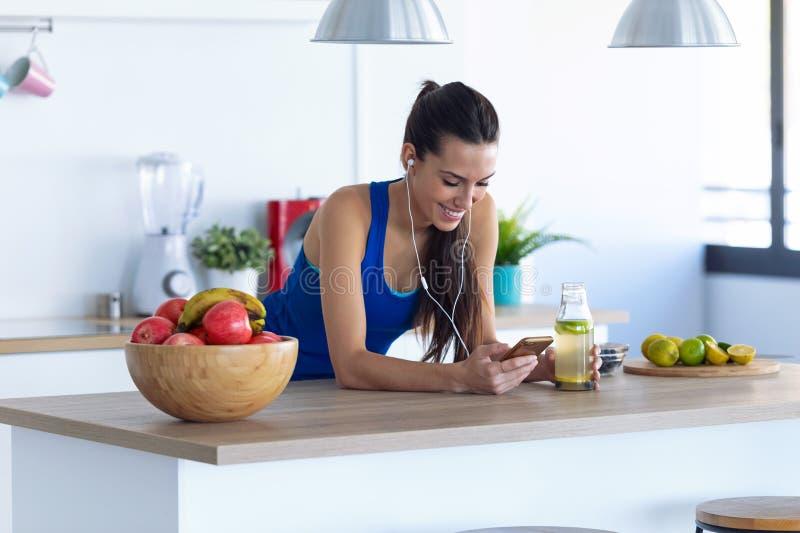 Sportig ung kvinna som lyssnar på musik med mobiltelefon efter träning i köket hemma fotografering för bildbyråer