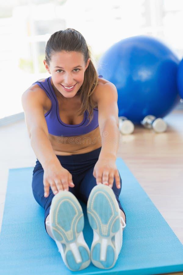 Sportig ung kvinna som sträcker händer till ben i konditionstudio royaltyfria foton