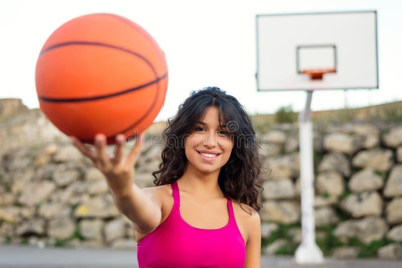 Sportig ung lycklig kvinna som spelar korgen royaltyfri fotografi