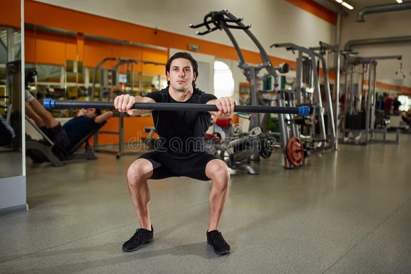 Sportig ung man i den svarta sportwearen med skivstången som böjer muskler i idrottshall royaltyfri bild