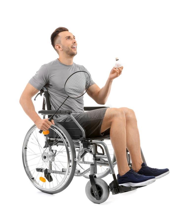 Sportig ung man med badmintonracket som sitter i rullstol på vit bakgrund royaltyfria foton