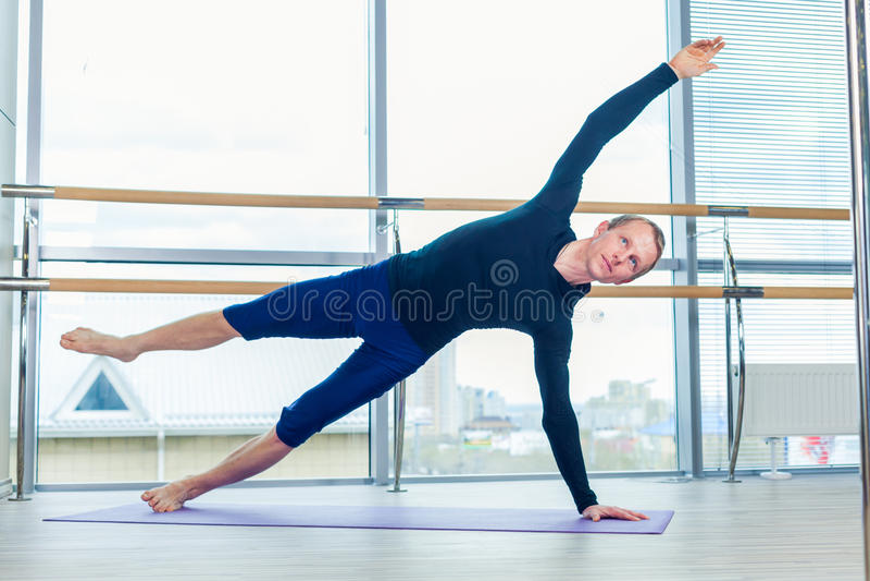 Sportig ung man som utarbetar, yoga, pilates, konditionutbildning som står i svanasana för mukha för adho för asanaekapada, en royaltyfri bild