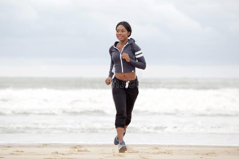 Sportig ung svart kvinna för full kropp som kör på stranden förbi vatten royaltyfria foton