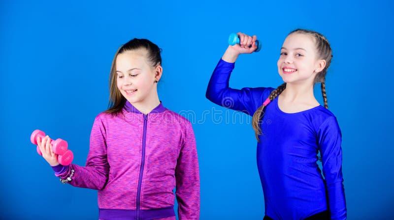 Sportig uppfostran L?tta ?vningar med hanteln P? v?g till starkare kropp Flickor som ?var med hantlar _ arkivbilder