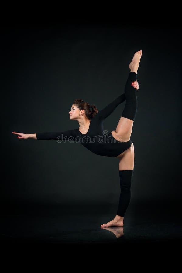 Sportig yogaflicka på svart bakgrund som gör övningssträckning arkivfoton