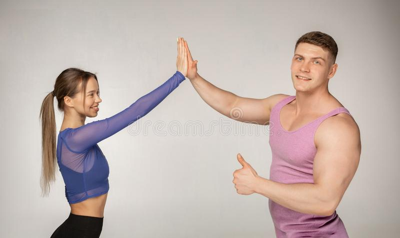 Sportiga attraktiva par i den moderiktiga sportswearen som till varandra ger höga fem fotografering för bildbyråer