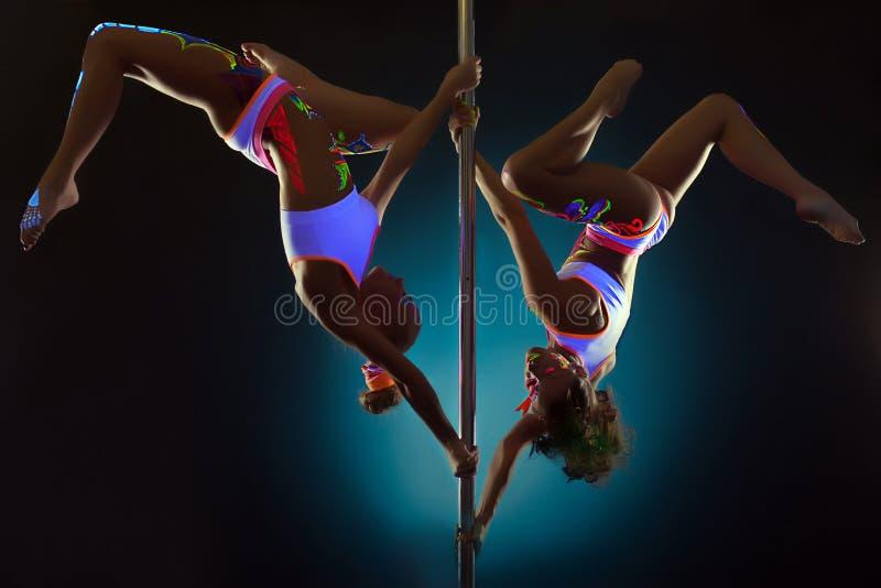 Sportiga flickor som dansar på pol under UV ljus arkivbild