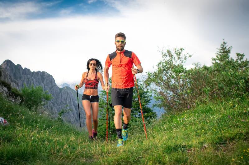 Sportiga par i bergen med nordiska gå poler royaltyfri fotografi