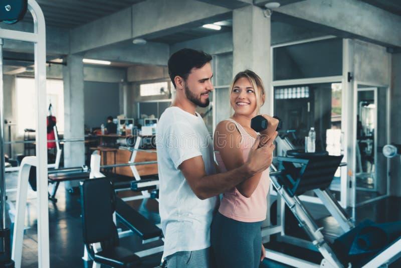 Sportiga par som övar att lyfta för hantelvikter i konditionidrottshall , Öva ståenden av attraktiva unga par genomkörare in arkivbild