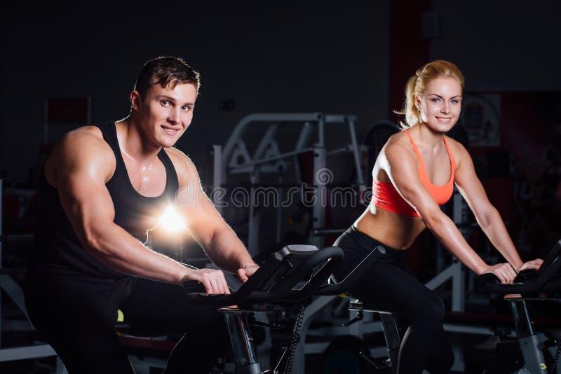 Sportiga par som övar på konditionen motionscykelen på en mörk idrottshall fotografering för bildbyråer