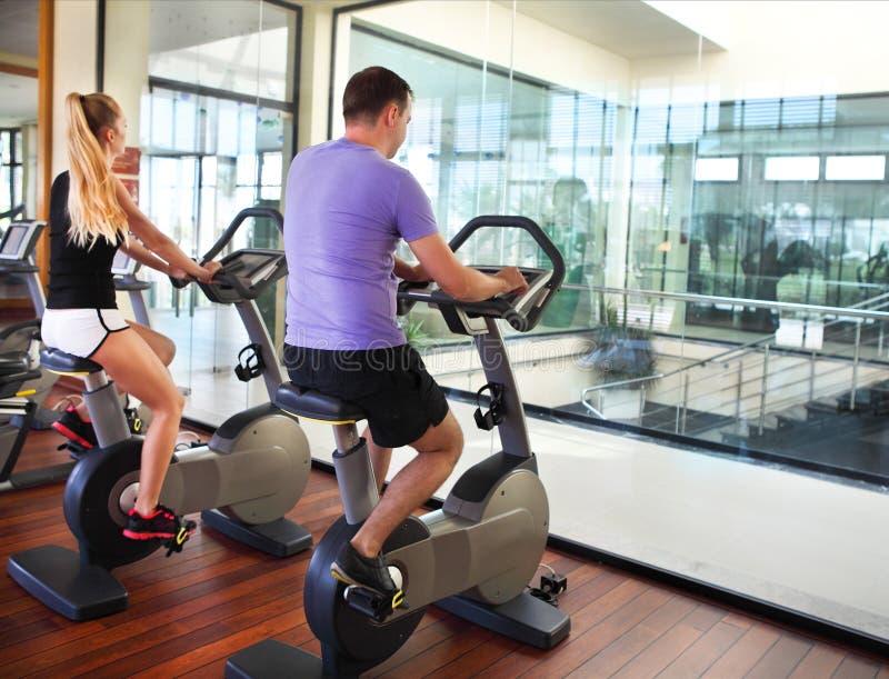 Sportiga par som övar på konditionidrottshallen royaltyfri foto
