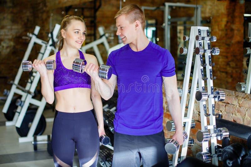 Sportiga par som övar på konditionidrottshallen Begreppet av kondition, sporten och den sunda livsstilen royaltyfria foton