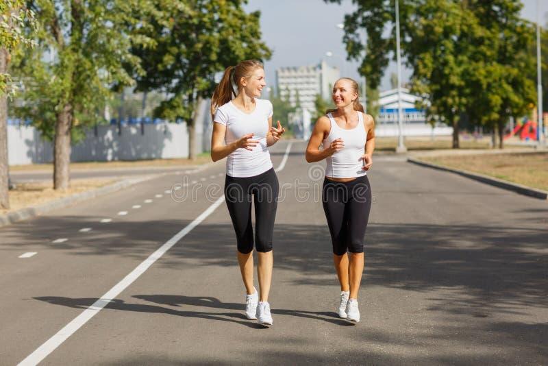 Sportiga unga flickor som kör på en parkerabakgrund Idrotts- sexiga kvinnor Jogga begrepp kopiera avstånd royaltyfri bild