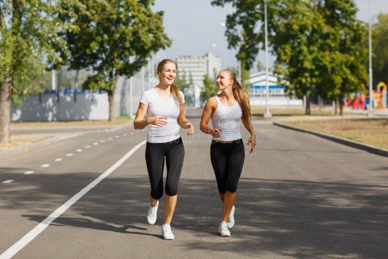 Sportiga unga flickor som kör på en parkerabakgrund Idrotts- sexiga kvinnor Jogga begrepp kopiera avstånd fotografering för bildbyråer