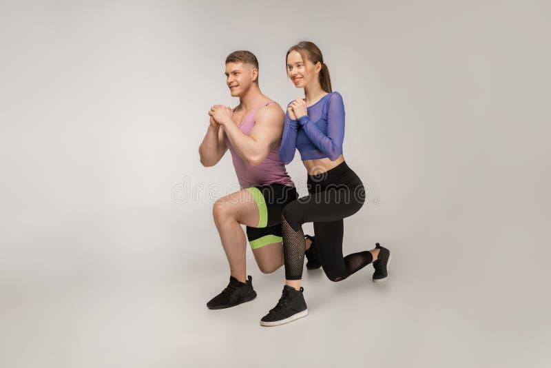 Sportiga unga par i den moderiktiga färgrika sportswearen som gör utfallet på vänster fot royaltyfri foto
