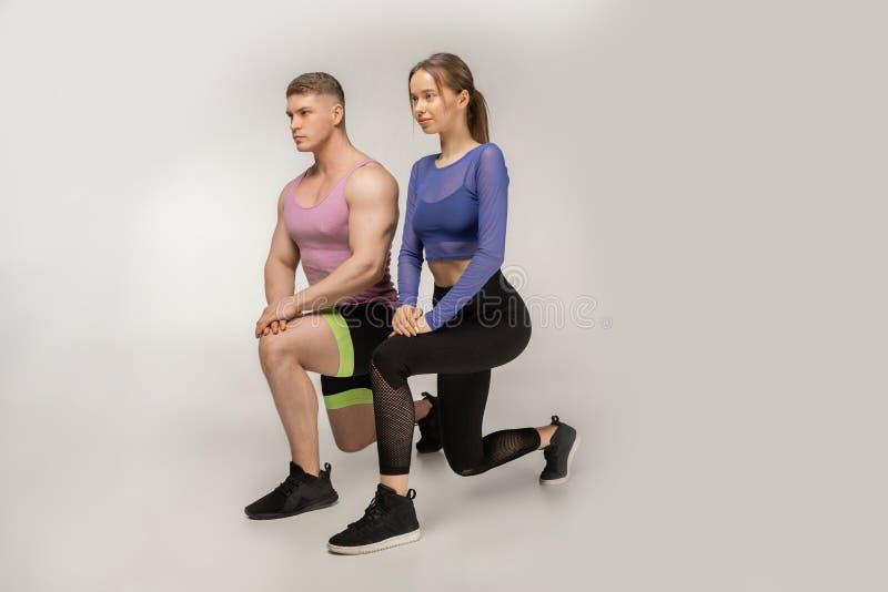 Sportiga unga par i den moderiktiga färgrika sportswearen som gör utfallet på vänster fot royaltyfri bild