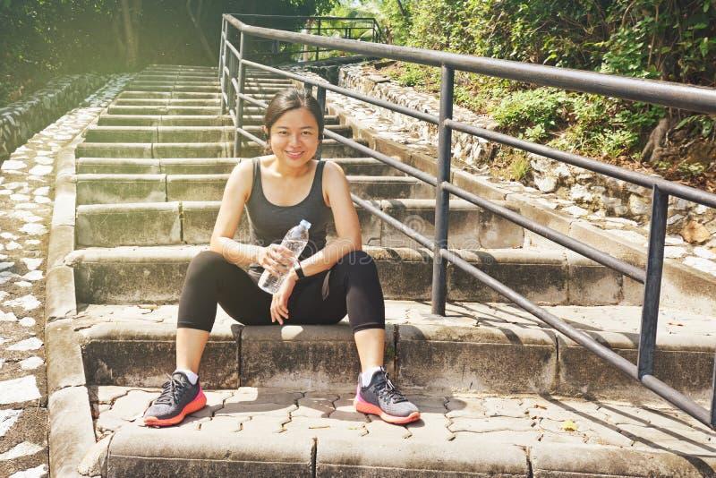 Sportigt asiatiskt kvinnasammanträde som vilar utomhus dricksvatten arkivbild