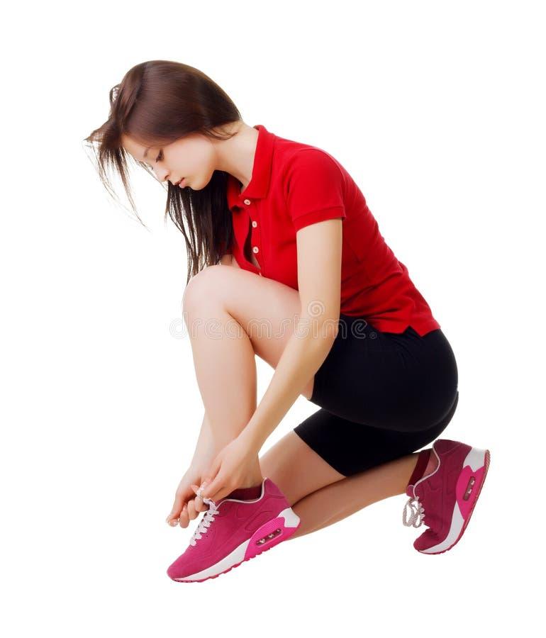Sportigt flickasammanträde som binder skosnöre Vit bakgrund royaltyfri bild