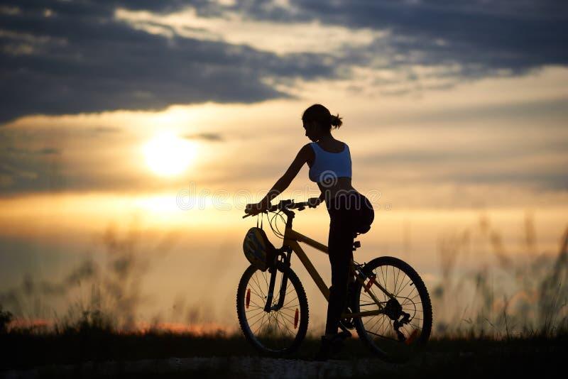 Sportigt kvinnasammanträde på cykeln och att posera royaltyfri fotografi