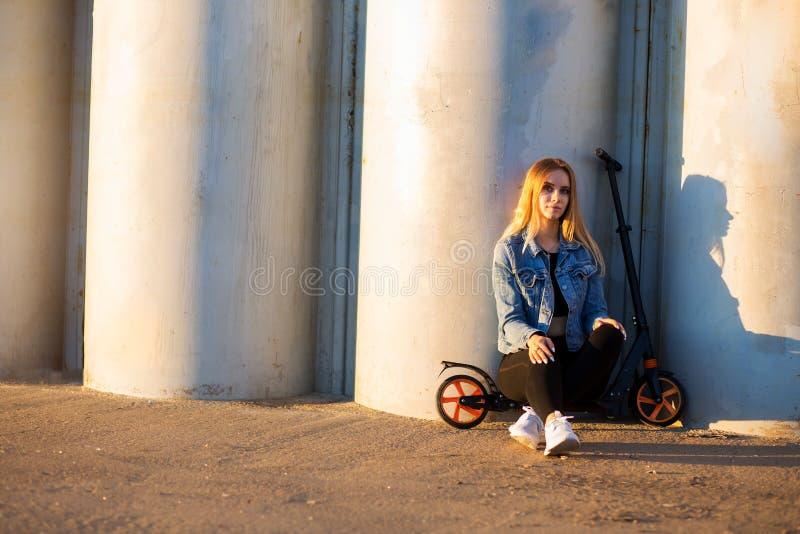 Sportigt kvinnasammanträde på en sparkcykel nära den gråa väggen royaltyfria foton