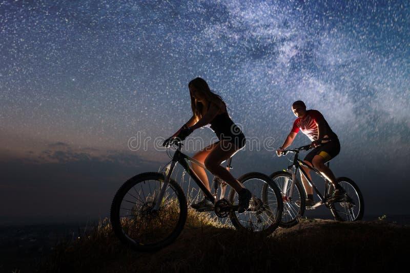 Sportigt rida för par cyklar på natten under stjärnklar himmel arkivbilder