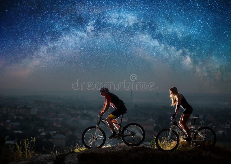 Sportigt rida för par cyklar på natten under stjärnklar himmel royaltyfria foton