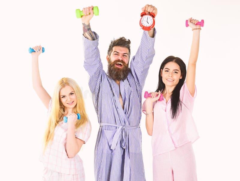Sportigt styrebegrepp Mannen i ämbetsdräkten, instruktörhåll tar tid på, attraktiva unga kvinnor i pyjamas som gör övningar med arkivfoto
