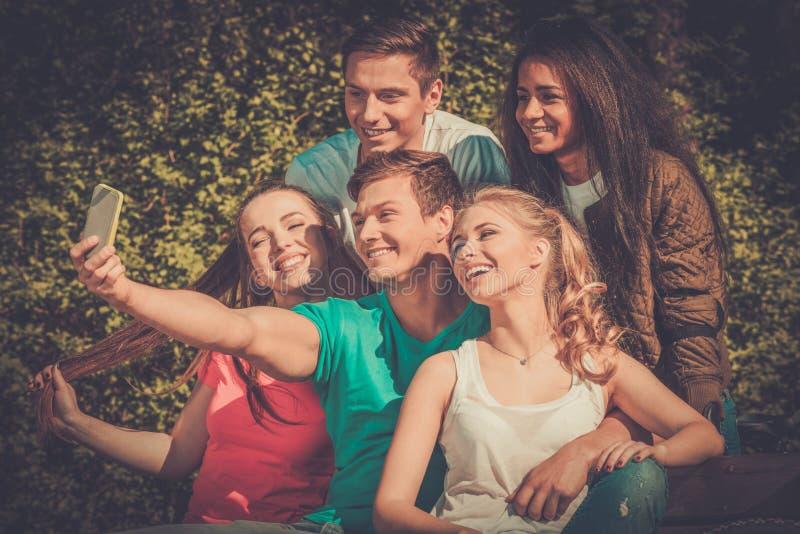 Sportigt tonårs- i en parkera som tar selfie royaltyfri fotografi