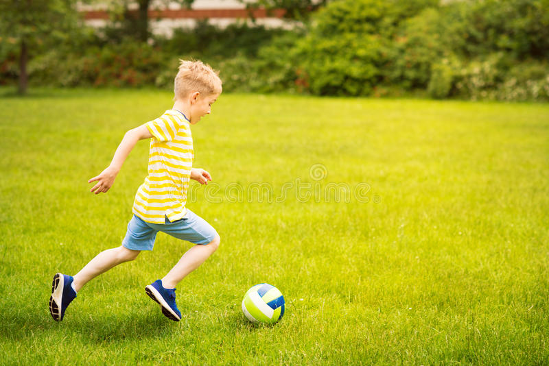 Sporting boy plays football in sunny park. Sporting little boy plays football in sunny park stock photography