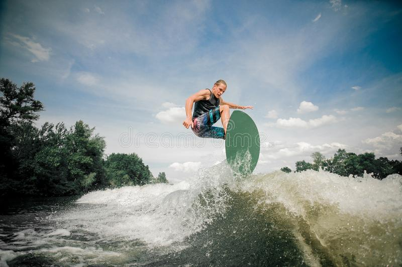 Wakeboarder rides up the wake. Sporting wakeboarder rides up the wake and the energy of the wake launches him airborne royalty free stock photography