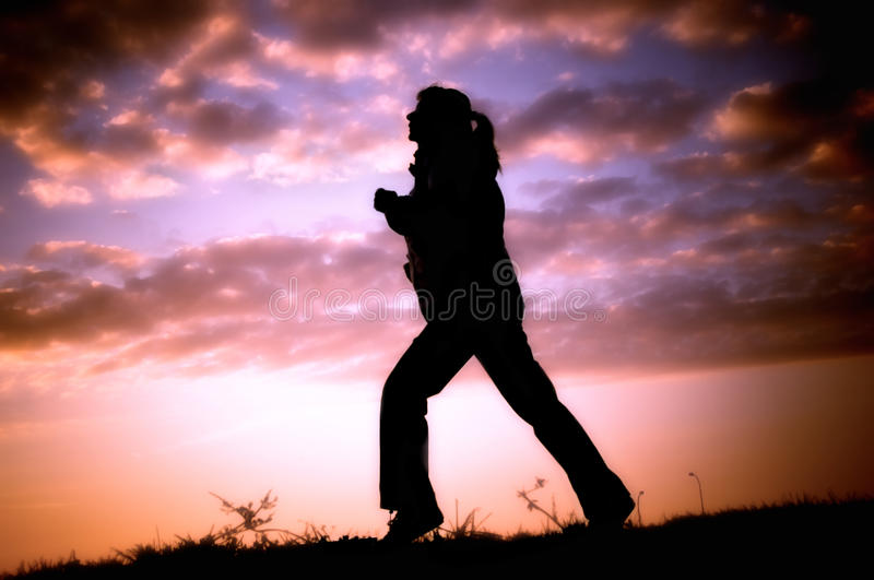 Sporting woman. Silhouette of sporting woman running outside over beautiful sunset royalty free stock photography