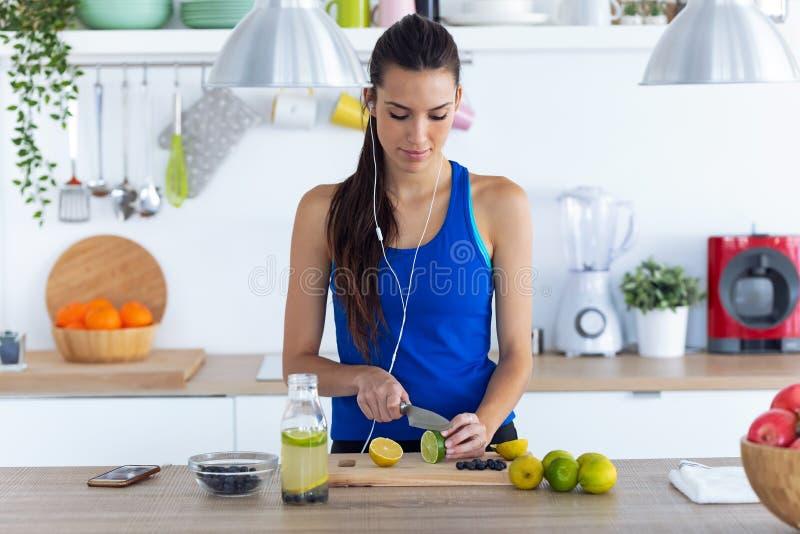 Sportio unga kvinnor skär limmar medan de lyssnar på musik i köket hemma arkivfoto