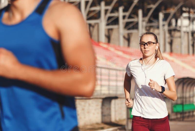 Sportish-Paare, die am Fußball-Stadion laufen stockfoto