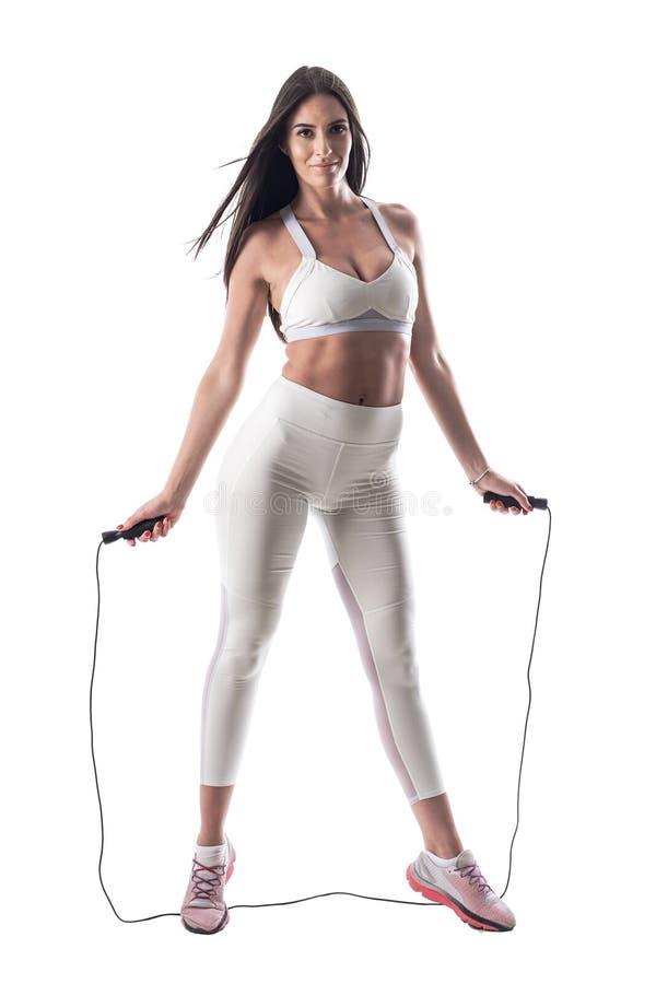 Sportiva adatta sportiva che posa mentre tenendo salto della corda o la corda di salto fotografie stock libere da diritti