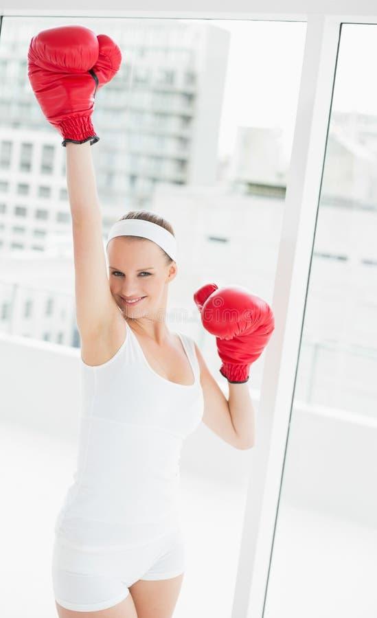 Sportiva graziosa incoraggiante che alza il suo guantone da pugile fotografia stock
