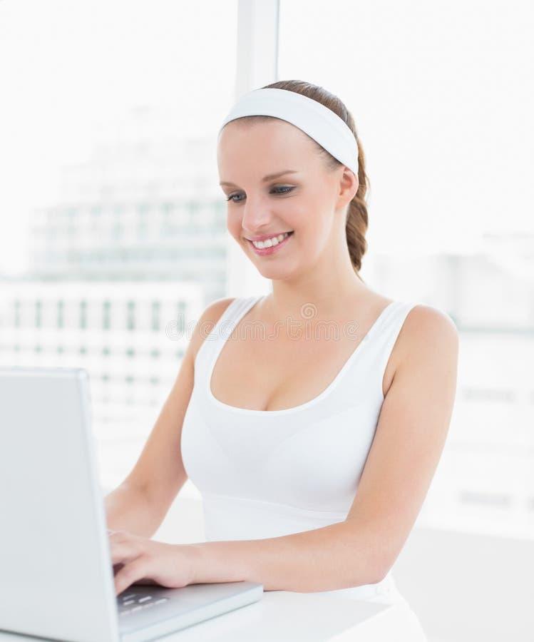 Sportiva graziosa rilassata che scrive su un computer portatile fotografia stock libera da diritti