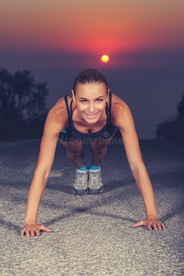 Sportive женщина делая pushups outdoors стоковые фото