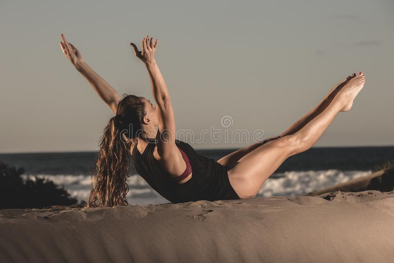 Sportive йога тренировки женщины на seashore стоковая фотография rf