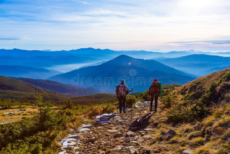 Sportive пары идя на заход солнца гор сельской дороги туманный стоковое фото rf