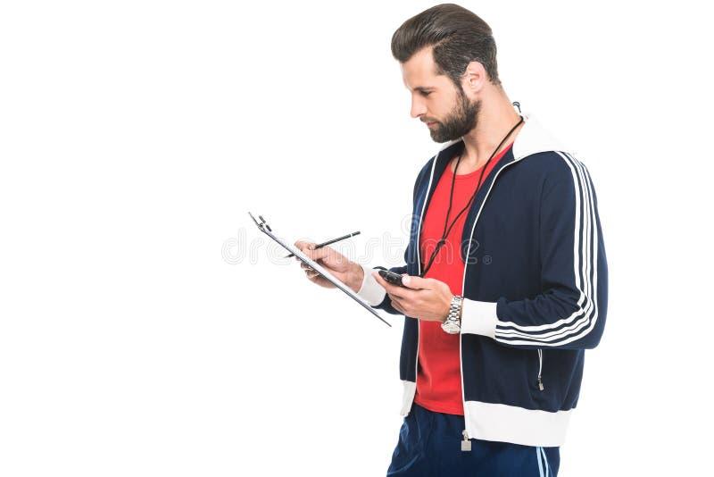 sportive тренер смотря секундомер и доску сзажимом для бумаги, стоковое фото