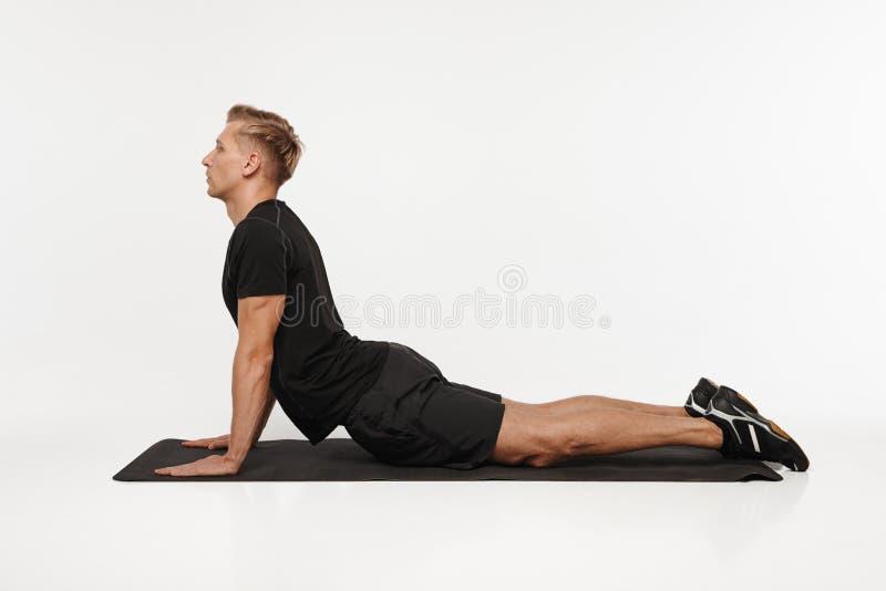 Sportive человек протягивая на циновке стоковое фото