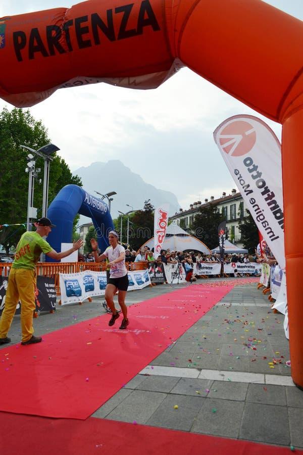 """Sportive arrivant à la finition """"ville de Lecco - d'événement courant de marathon de montagne de Resegone """" image libre de droits"""