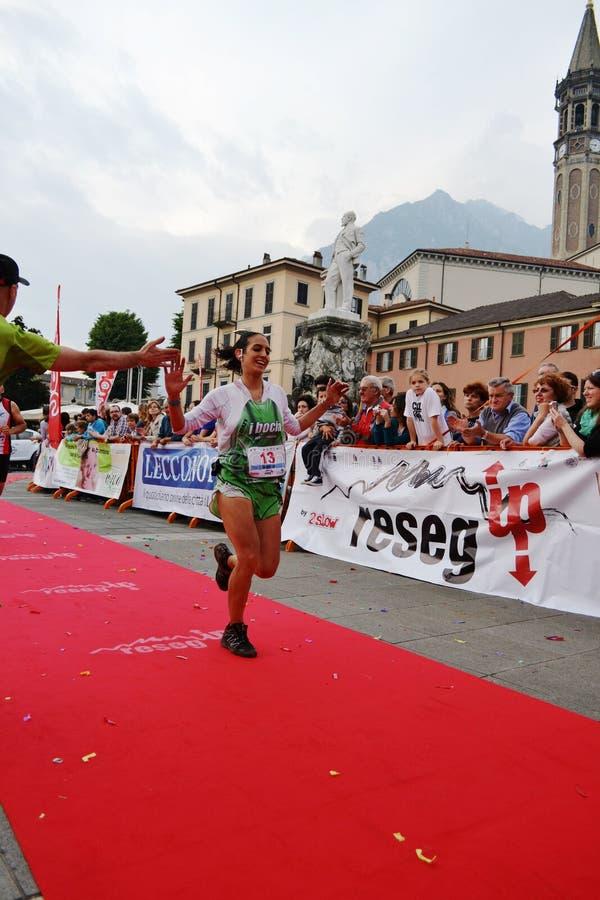 """Sportive arrivant à la finition """"ville de Lecco - d'événement courant de marathon de montagne de Resegone """" image stock"""