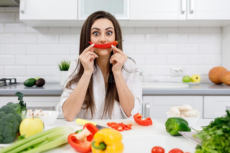 Sportive Brunette Posing With a Chili Pepper Moustache. Sportive brunette beauty posing at the kitchen table with a chili pepper moustache stock images