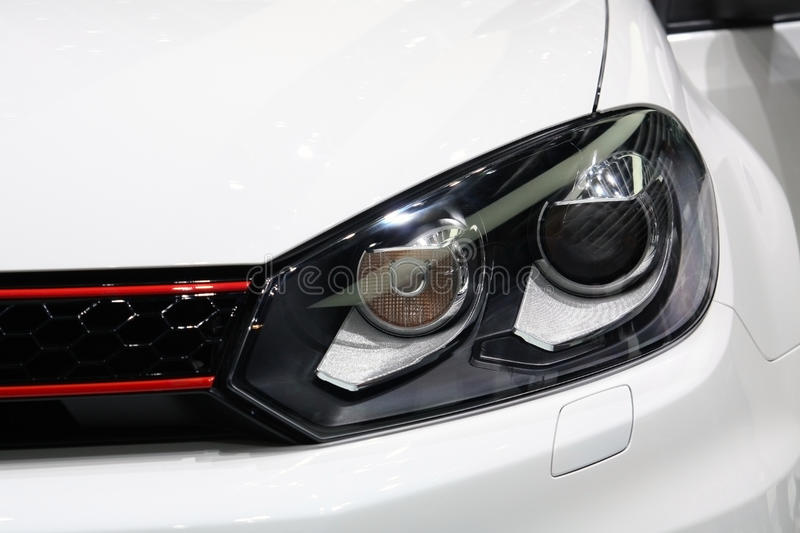 Sportive car headlight detail. Detail of a car headlight of sportive nature. Plain white car color. Shallow depht of field with focus on the light sources of the royalty free stock photos
