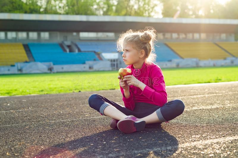 Sportive child girl eat apple. Beautiful young athletic sportive child girl eat apple, sitting after the training. Healthy natural food for sports kid stock images