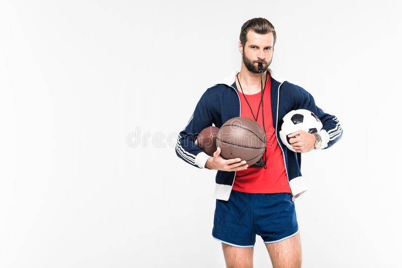 sportive coach with whistle holding rugby, basketball and soccer balls, stock photography